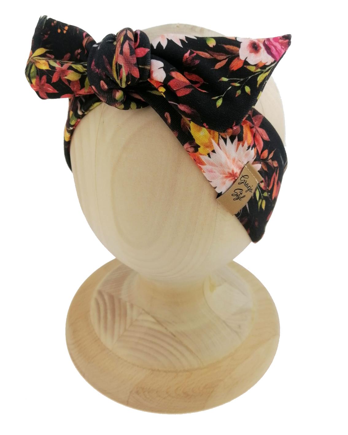 Opaska kobieca typu Pin-up marki Gracja Styl. Uszyta z bawełny petelkowej typu dresówka. Wzór opaski kwiaty na czarnym tle.