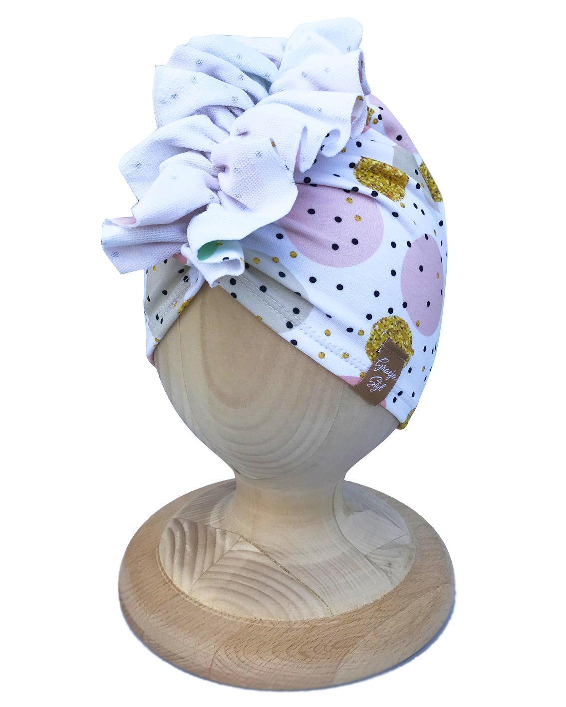 Czapka Turban piękna ozdoba główki dla malucha jak i zarówno dla starszych dziewczynek. Wykonany z elastycznej dresówki idealne zarówno na upały oraz zimniejsze dni. Super zamiennik dla czapek chust, kapeluszy. Dzięki zastosowaniu wysokiej jakości dresówki oraz domieszce elastanu dzianina dobrze się układa, zapobiega przesunięciu się a co za tym idzie w trakcie użytkowania nie zsuwa się z USZÓW. Absolutny must have sezonu.